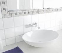 helle Bordüre umrahmt den Badezimmerspiegel zwischen weißen Wandfliesen